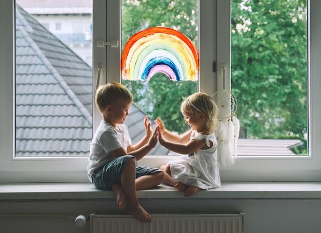 Lachende kleine kinderen op de achtergrond van het schilderen van de regenboog op het raam
