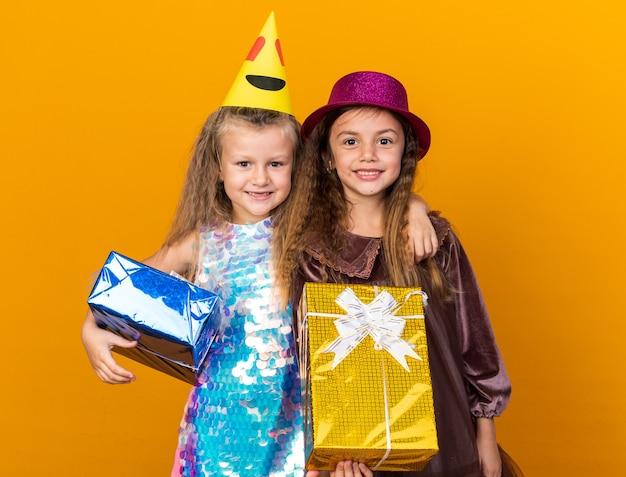 Lachende kleine mooie meisjes met feestmutsen die hun geschenkdozen houden geïsoleerd op een oranje muur met kopieerruimte