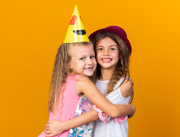 Lachende kleine mooie meisjes met feestmutsen knuffelen elkaar geïsoleerd op oranje muur met kopieerruimte copy