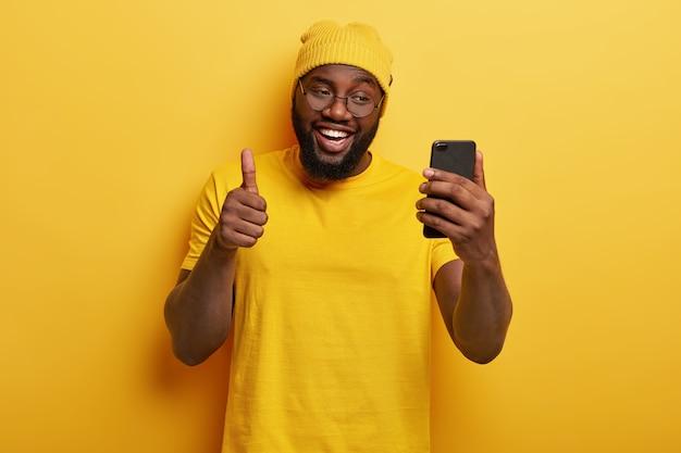 Lachende knappe man met bril poseren met zijn telefoon