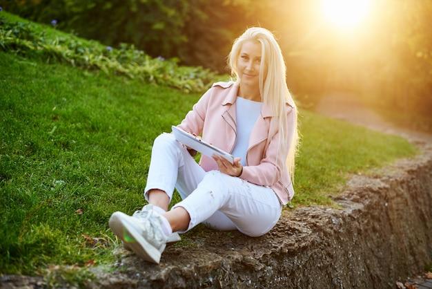 Lachende knappe vrouw luisteren ontspannende muziek in de koptelefoon met haar mobiele telefoon of tablet in het park. student luistert naar een online college en bereidt zich voor op tentamens.