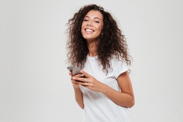 Lachende krullend vrouw met smartphone in handen