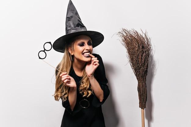 Lachende krullende heks die van halloween geniet. binnenportret van goedgehumeurde tovenaar die op witte muur wordt geïsoleerd.