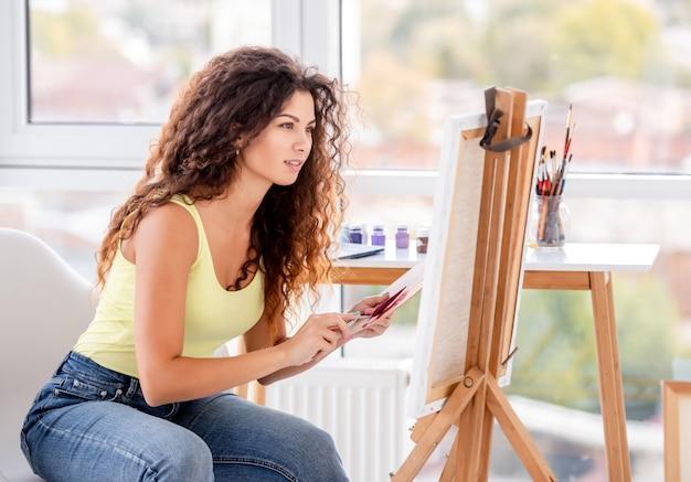 Lachende kunstenaar schilderij op ezel
