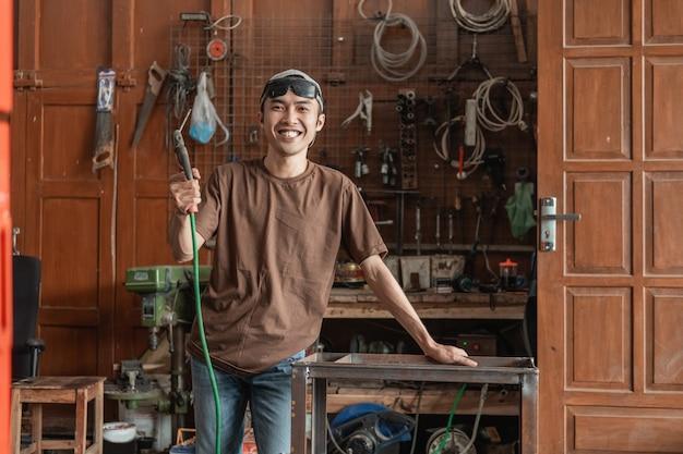 Lachende lasser kijkt in de camera terwijl hij een elektrische lasser vasthoudt in een laswerkplaats
