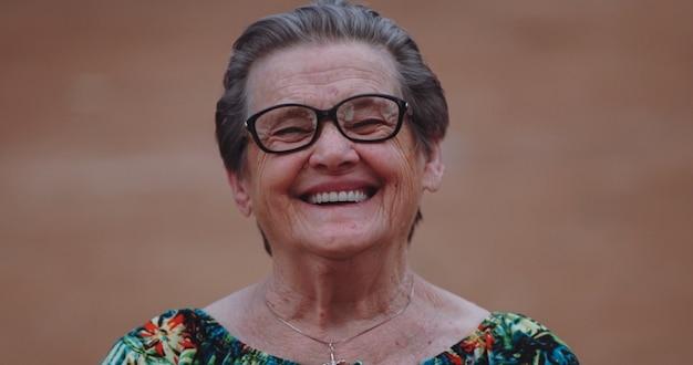 Lachende latijnse oudere vrouw die naar de camera kijkt