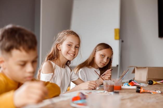 Lachende leerlingen schilderen op papier met kleurrijke verf