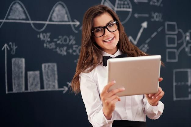 Lachende leraar met behulp van digitale tablet in de klas
