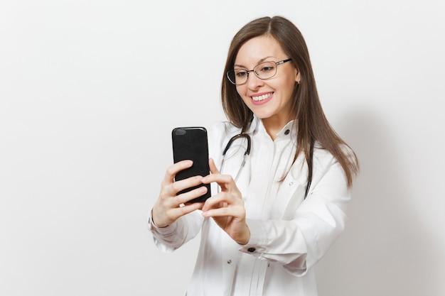 Lachende leuke mooie jonge dokter vrouw met stethoscoop, bril geïsoleerd op een witte achtergrond. vrouwelijke arts in medische jurk die selfie op mobiele telefoon doet. zorgpersoneel, gezondheid, geneeskunde conc