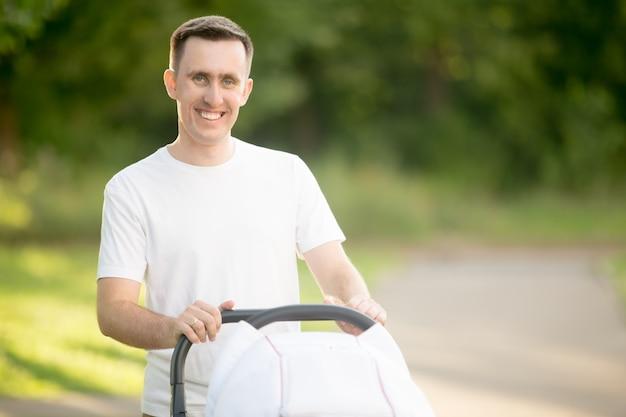 Lachende man die een kinderwagen
