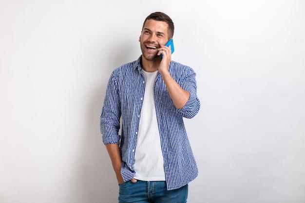 Lachende man die met een smartphone spreekt en omhoog kijkt
