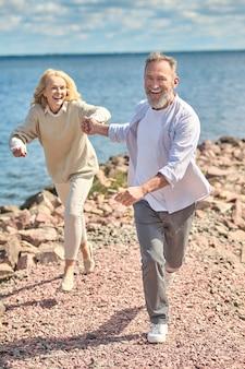 Lachende man en vrouw die in de buurt van water rennen