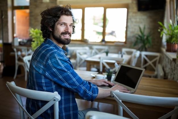 Lachende man met behulp van laptop in koffiewinkel