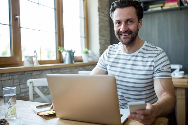 Lachende man met behulp van zijn laptop en mobiele telefoon in de koffiebar