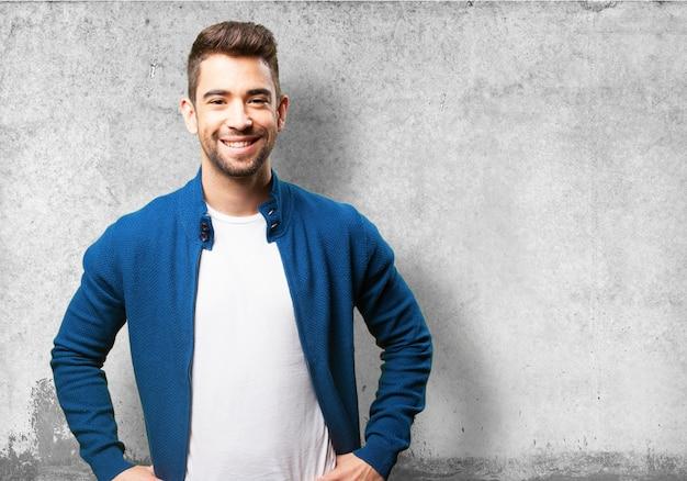 Lachende man met de handen op de heupen op een grijze achtergrond