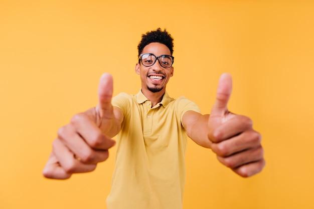 Lachende man met kort kapsel duimen opdagen. indoor foto van knappe afrikaanse man.