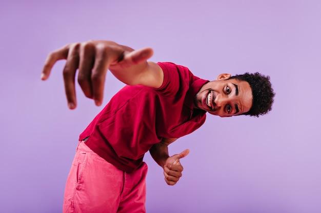 Lachende man met korte haarstijl koelen. zorgeloze zwarte kerel in roze broek die voor de gek houdt.
