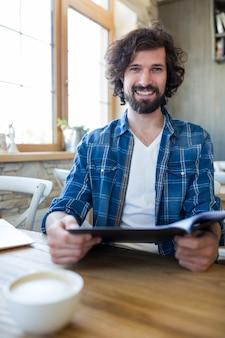 Lachende man met menu in koffiebar