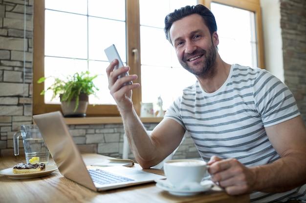 Lachende man met mobiele telefoon en kopje koffie in de koffiebar