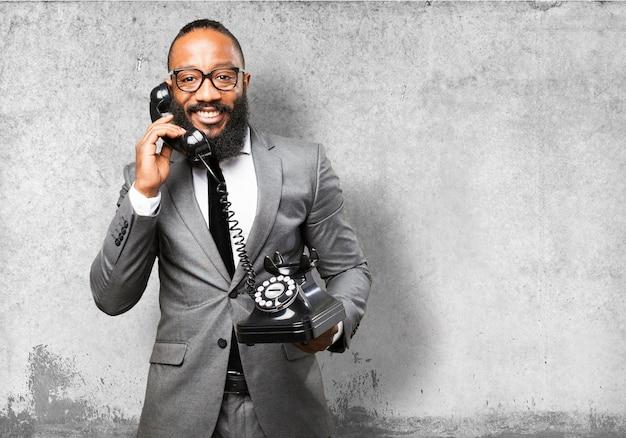 Lachende man met pak praten over de telefoon