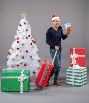 Lachende man met zijn koffer en reistickets op grijs