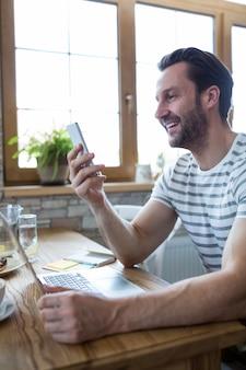 Lachende man op zoek naar zijn mobiele telefoon in de koffiebar