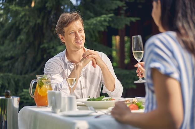 Lachende man rust met vrolijke dame aan de eettafel in de buitenlucht