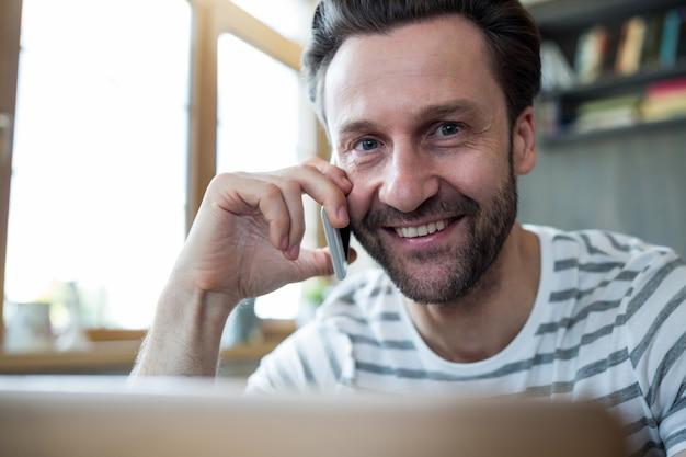 Lachende man te praten op de mobiele telefoon in de koffiebar