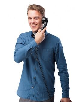 Lachende man te praten over een oude telefoon