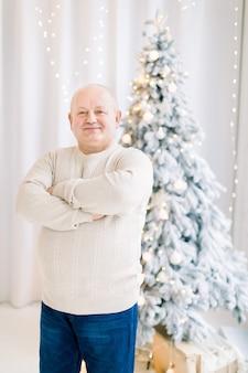 Lachende man van middelbare leeftijd die op de achtergrond van de kerstboom