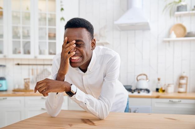 Lachende man zit aan de balie in de keuken. vrolijke mannelijke persoon poseert 's ochtends thuis aan tafel