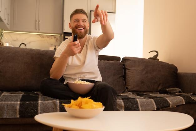 Lachende man zit op de bank en kijkt tv of film. jonge europese man wijst met vinger, houdt afstandsbediening vast en kom met popcorn. concept van thuis rusten. interieur van studio appartement