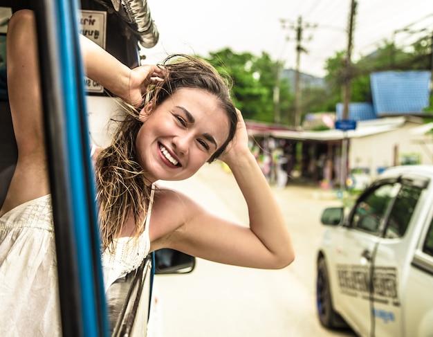 Lachende meisje kijkt uit het raam van een taxi, tuk-tuk