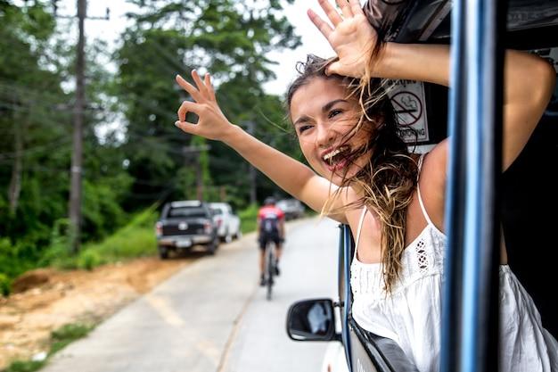 Lachende meisje kijkt uit het raam van een taxi