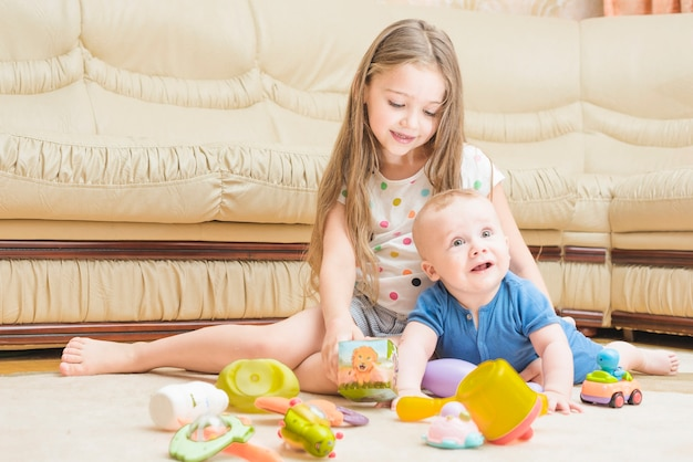 Lachende meisje speelt met haar broer of zus baby op tapijt
