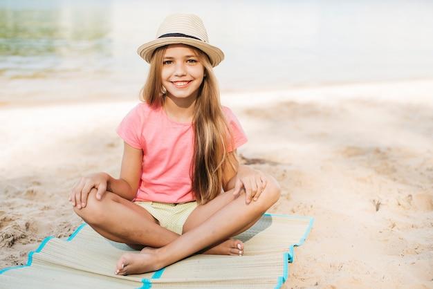Lachende meisje, zittend aan een strand