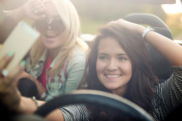 Lachende meisjes in een auto