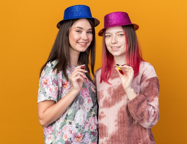 Lachende meisjes met feestmuts met feestfluitje geïsoleerd op oranje muur