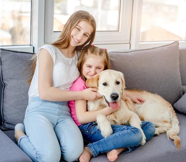 Lachende meisjes mooie hond knuffelen in lichte kamer