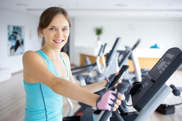 Lachende meisjes opleiding op oefening machine in gym