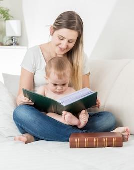Lachende moeder die een verhaal voorleest aan haar 9 maanden oude babyjongen