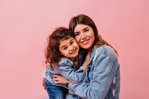 Lachende moeder en dochter camera kijken. vooraanzicht van jonge vrouw met preteen kind dat op roze achtergrond wordt geïsoleerd.