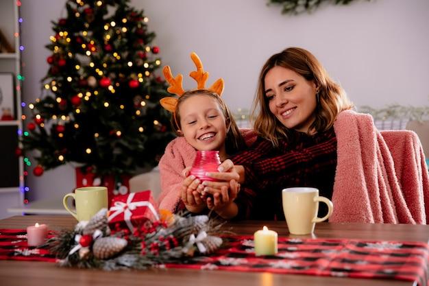Lachende moeder en dochter houden en kijken naar kaars zittend aan tafel genieten van de kersttijd thuis