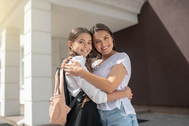 Lachende moeder en dochter in schooluniform knuffelen staande in de buurt van school op zonnige ochtend