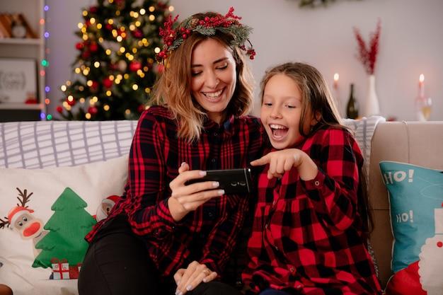 Lachende moeder en dochter kijken naar iets op telefoon zittend op de bank en genieten van kersttijd thuis