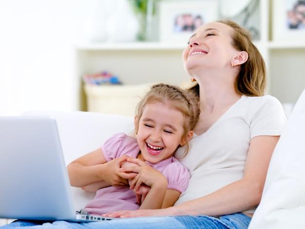 Lachende moeder en dochter met laptop