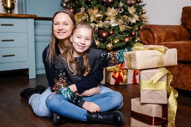 Lachende moeder en dochter met veel geschenkdozen thuis
