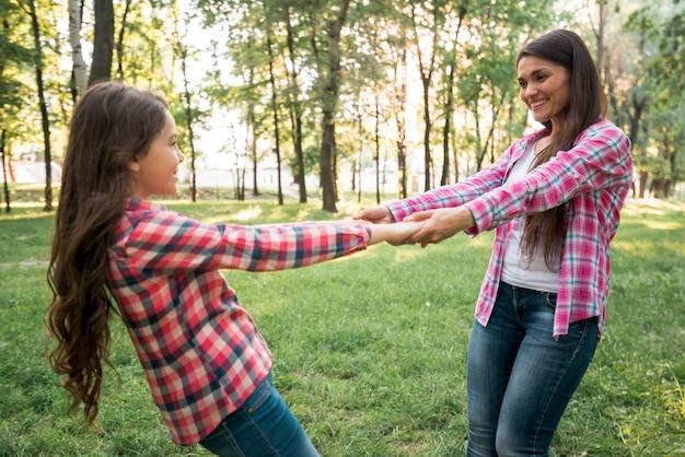 Lachende moeder en dochter spelen in park