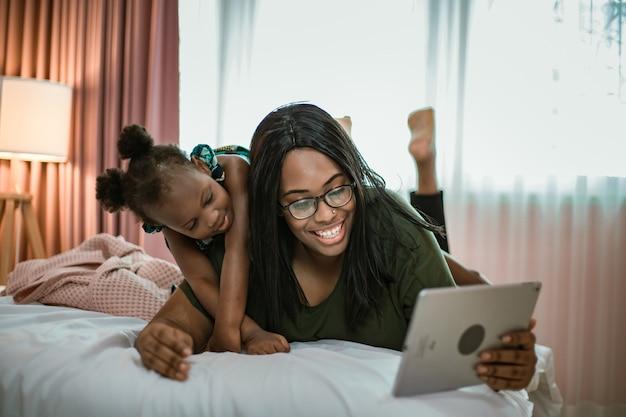 Lachende moeder en dochtertje met behulp van computertablet, samen video-oproep.