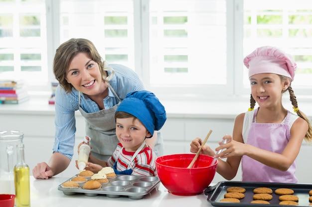 Lachende moeder en kinderen bereiden van cookies in de keuken